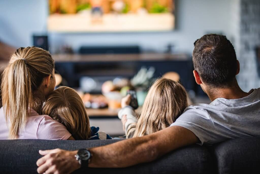 Back view of a relaxed family watching TV on sofa in the living room