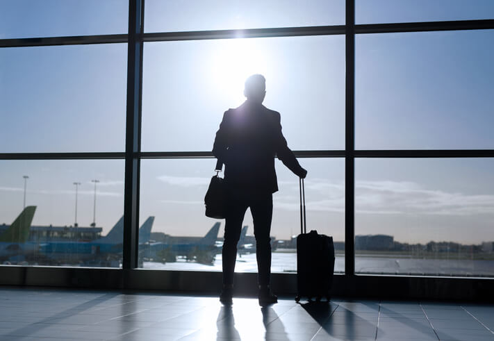 Silhouette of businessman standing with suitcase in airport