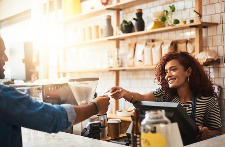 Business owner accepting a credit card payment from a customer in a cafe