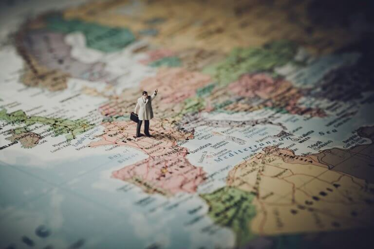 Close up shot of a person figurine standing on top a map of France