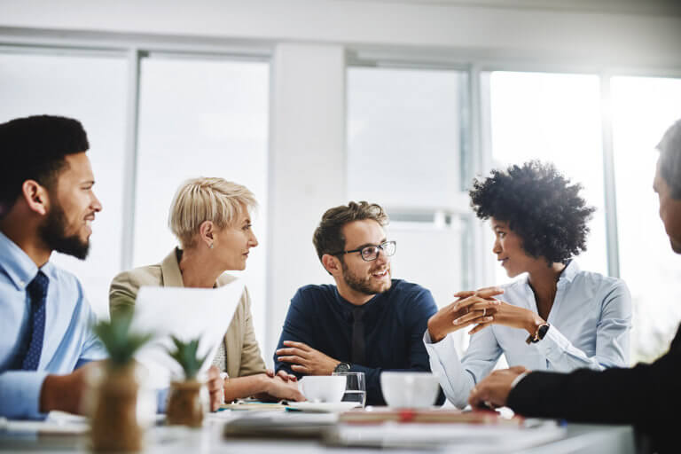 Diverse group of businesspeople sitting together and having a meeting in the office