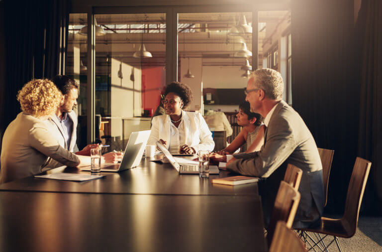 Group of diverse businesspeople meeting around a boardroom table