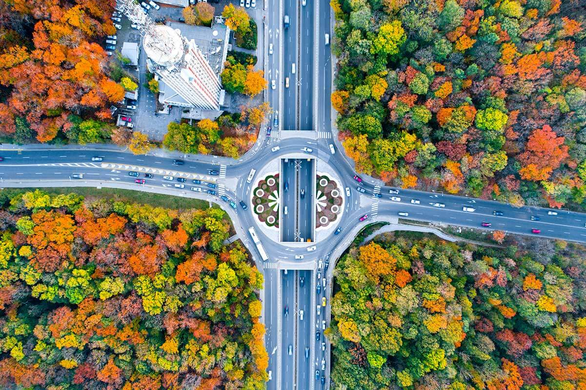 Aerial eagle eye view of a traffic circle roundabout located between beautiful autumn forest